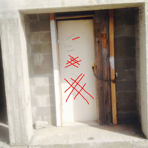 Stanza chiusa con catena con evidenti scritte e disegni riguardo il suo utilizzo